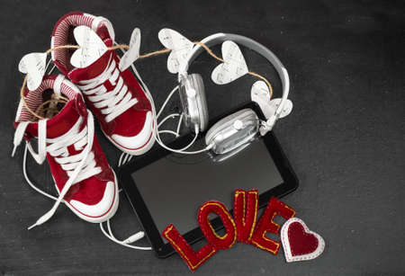 Love for music concept. Red sneakers, headphones, tablet and hearts with notes on the blackboard.