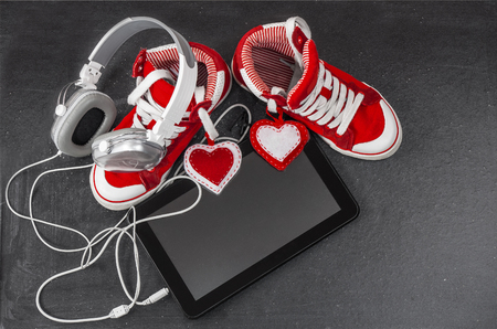 Love for music concept. Red sneakers, headphones, tablet .