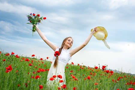 Photo pour teenage girl standing in a field with wild poppies in a hat looking into the distance - image libre de droit