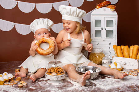 Photo pour two little girls sisters in chef costumes in the studio with bakery products. The chef plays in the studio. - image libre de droit