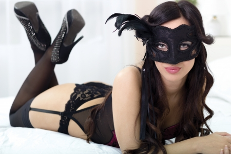 Photo pour Portrait of attractive sensual young woman in black lingerie on bed with mask - image libre de droit