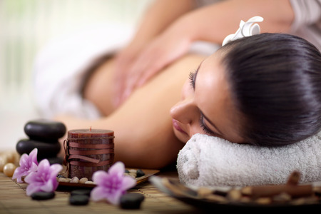 Beautiful woman having a wellness back massage at spa salonの写真素材