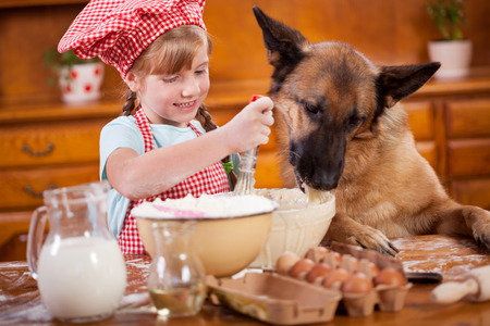 Photo for a little girl and her friend dog make a mess in the kitchen - Royalty Free Image