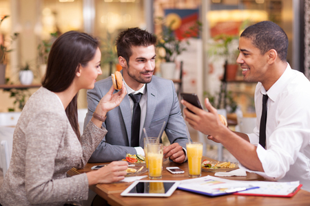 Photo pour Three Business people Having Meeting In Outdoor Restaurant - image libre de droit