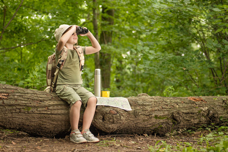 excited little girl on a camping trip in green forest