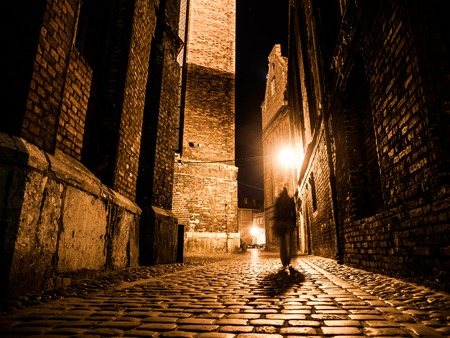 Illuminated cobbled street with light reflections on cobblestones in old historical city by night. Dark blurred silhouette of person evokes Jack the Ripper.