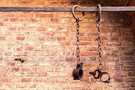 Middle aged prisoners chains and cuffs over a brick wall