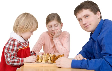Man and childs play to chess on a white background