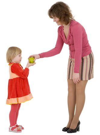 Women give green apple to the girl on white