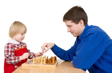 Man and girl play chess on white