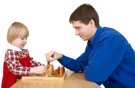 Man and child play chess on white