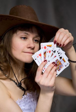 Portrait girl with a playing-cards in hand on black