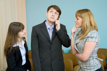 The man speaks by a mobile phone in the presence of two girls