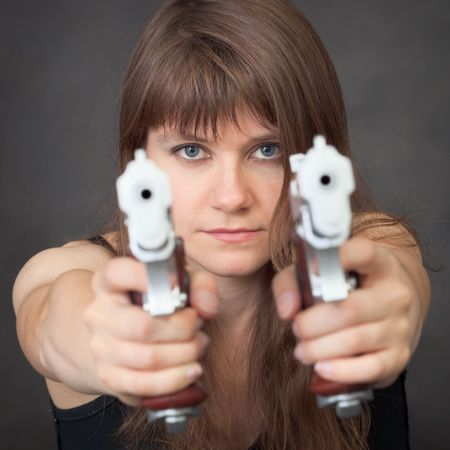 The serious girl aims from two big pistols close up