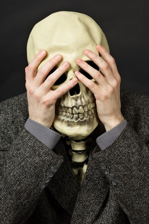 Skeleton covering his eyes on a dark background