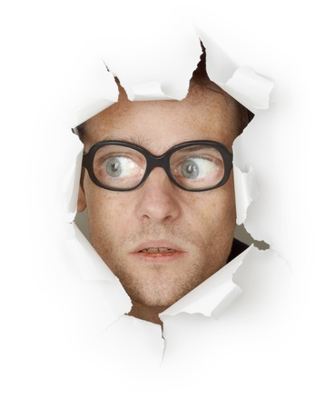 Funny man in an old-fashioned glasses looking out of the hole isolated on white background