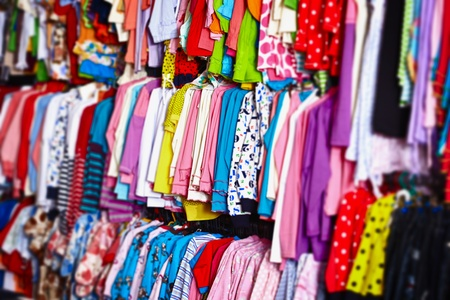Foto de Colorful baby clothes hanging on hangers in a store - Imagen libre de derechos