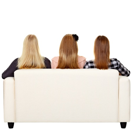 Young women sitting on sofa - rear view. Isolated on whiteの写真素材