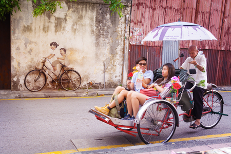 MALAYSIA, PENANG, GEORGETOWN - CIRCA JUL 2014: A real bicycle, juxtaposed over a lifesize mural of a bicycle, and tourists in a pedicab.