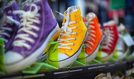 Photo pour Collection of colorful casual gumshoes on shelves in the fashion store - image libre de droit