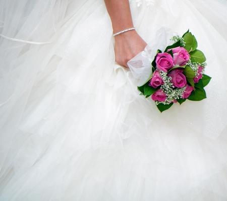 Photo pour bridal bouquet on a background of white wedding dresses - image libre de droit
