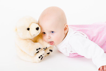 blue-eyed baby with a soft toy.