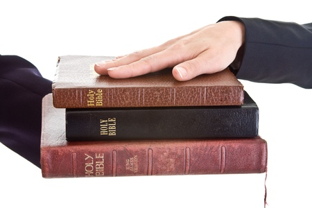 Woman's hand resting on a stack of bibles.  Swearing on a stack of bibles theme.