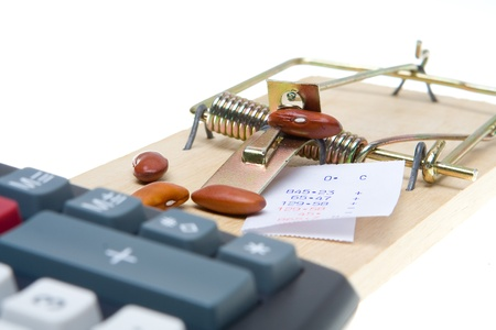 Mousetrap baited with beans and adding machine tape to trap an accountant.  Isolated on white background.