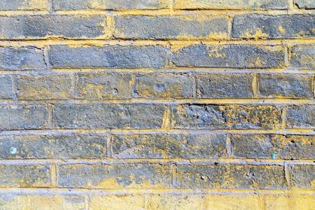 Rough gray brick yellow painted wallの写真素材