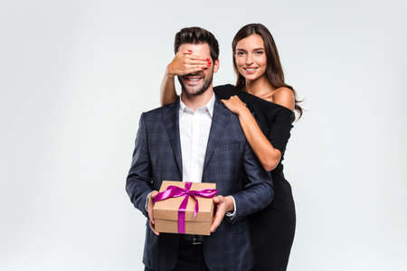 Photo pour Just don't look a minute! Young handsome men holding a gift box while his girlfriend covering his eyes with her hand and looking at camera with smile - image libre de droit
