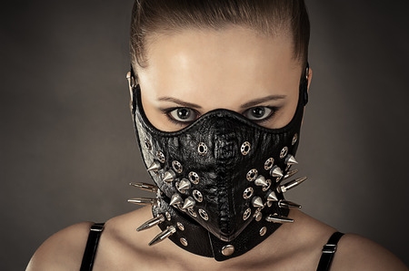 portrait of a woman in a mask with spikes isolated on gray