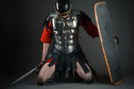tired soldier kneeling with a shield and a sword in hands