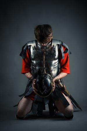 man kneeling with a helmet in hands