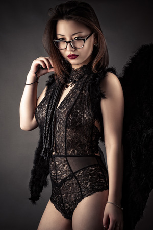 luxurious woman with whip in hands with black wings