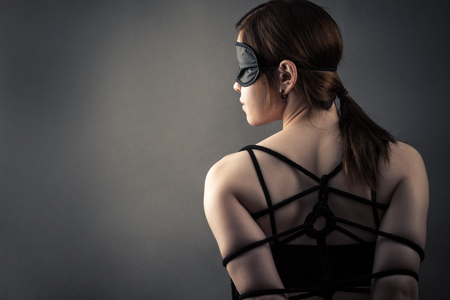 Beautiful woman in mask and bondage