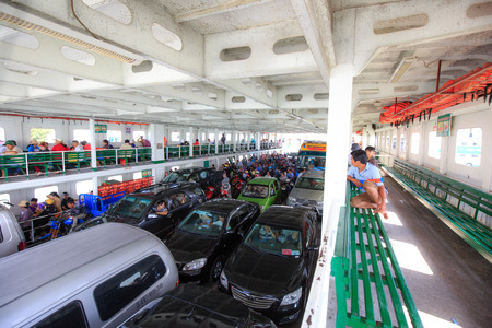Ho Chi Minh City, Vietnam - June 27, 2015 - People on the ferry transporting and oto in HoChiMinh City, Vietnam