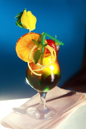 Appealing cool fruity cocktail with blue background
