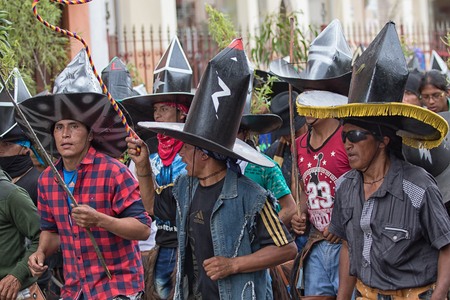 June 29, 2017 Cotacachi, Ecuador: indigenous men wearing extra large sombreros dancing in  the main square of the town at Inti Raymi