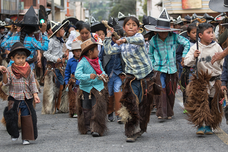 June 24, 2017 Cotacachi, Ecuador: indigenous quechua children wearing chaps and sombreros participating at the Inti Raymi parade