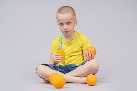 Smiling boy sitting with fruit orange and drink. Isolated on gray