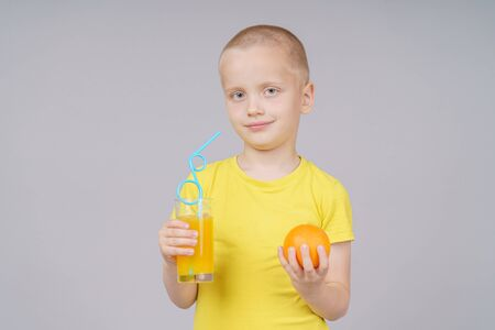 Smiling boy standing with fruit orange and drink. Isolated on gray