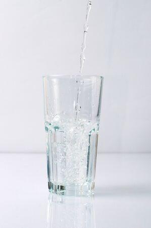 Photo pour Splashing liquid water is pouring into a glass - image libre de droit