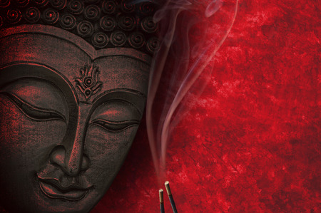 Buddha image with red background and incense