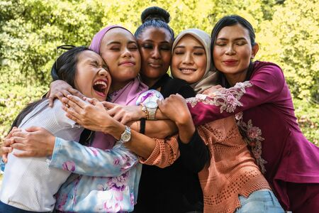 Photo pour Five female friends of different ethnicity and faiths embrace each other in a group hug - image libre de droit