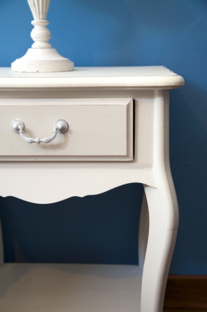 white bedside table and lamp with blue lampshade