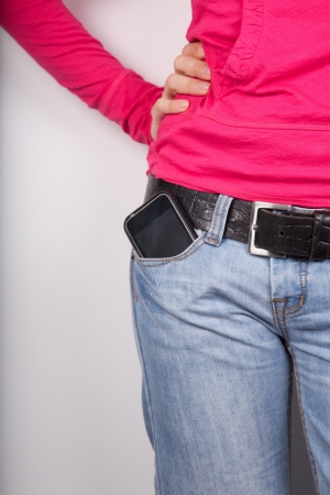 woman pink shirt detail with smartphone in her pocket jeans