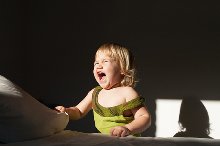portrait of blonde caucasian baby two years old standing with green dress open mouth screaming and shouting sunlight on the face in dark room indoor