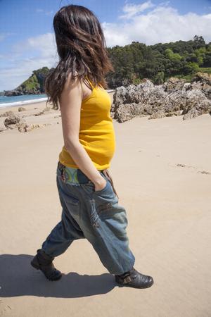 walking pregnant woman with yellow shirt at Asturian beach