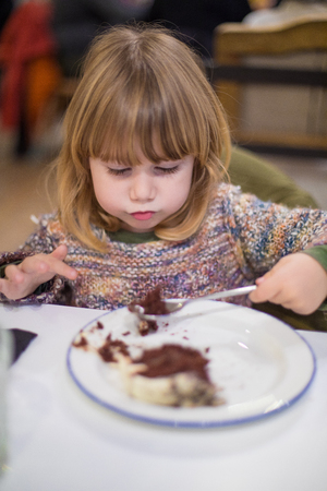 Three years old blonde cute caucasian child with knitted sweater eating chocolate cake piece with spoon, in white dish at restaurant