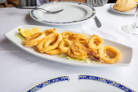 Foto de white tray with rings of squid, breaded and fried, with lemon and lettuce, typical food of Andalusia (Spain, Europe) on white tablecloth of restaurant ready to eat - Imagen libre de derechos